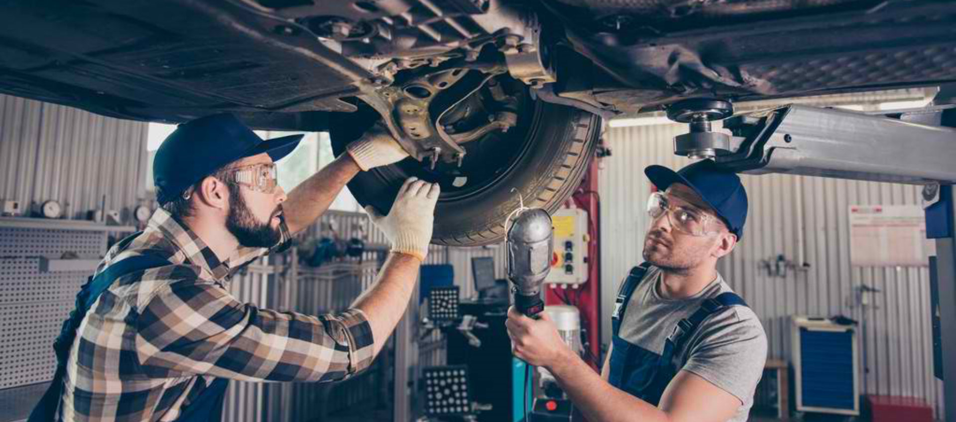 two men mechanics are working together to fixed the break of a car