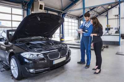 car mechanic and customer stand next to the serviced car and looking through the checklist