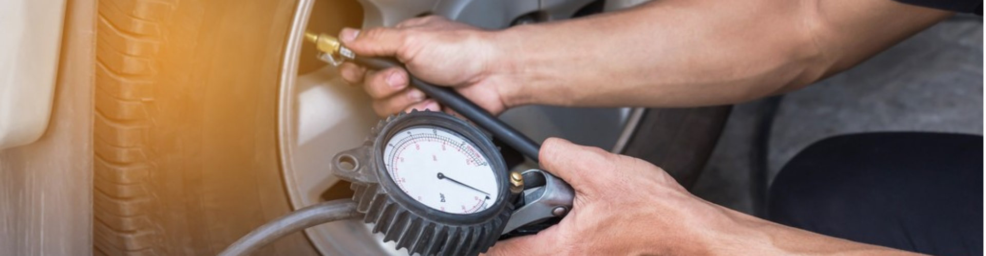mechanic inflating tire and checking air pressure with gauge pressure in service station