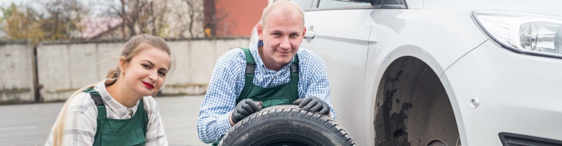 two mechanics at car service with spare wheel