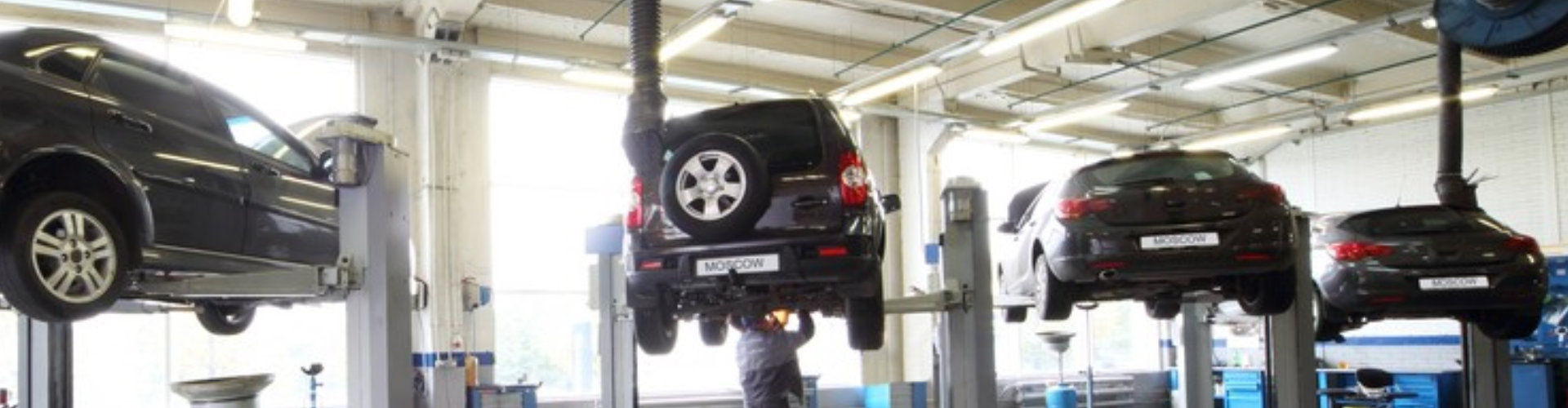 four black cars on lifts in small service station and two men repair one car