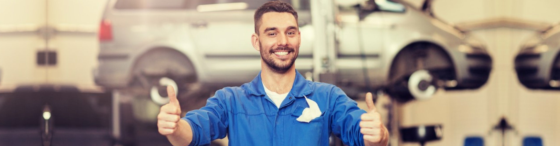 male smiling mechanic doing a thumbs up